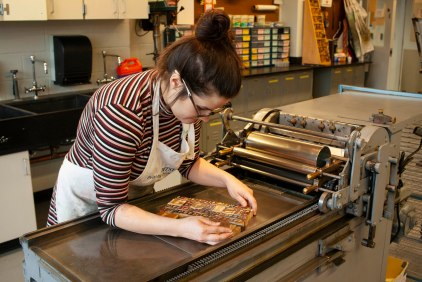 Violet Stubbs moves type to the press.