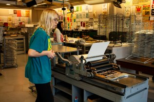 Sophie Hall pulls the paper through the press. Yuelin Chen works in the background.